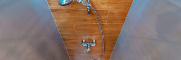 Elegant and Modern Bathroom Shower Cabin. Wide Angle Photo. Wood Imitation Bathroom Tiles.