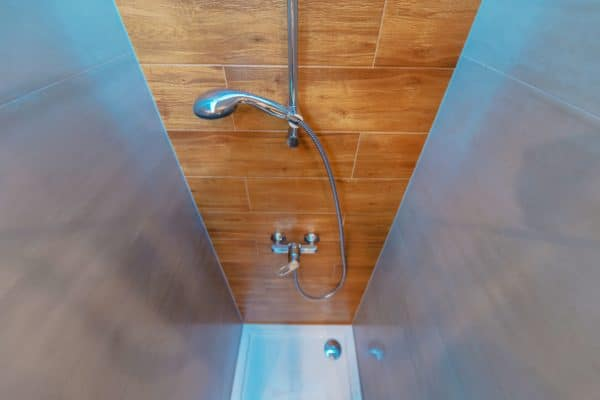 Elegant and Modern Bathroom Shower Cabin. Wide Angle Photo. Wood Imitation Bathroom Tiles.